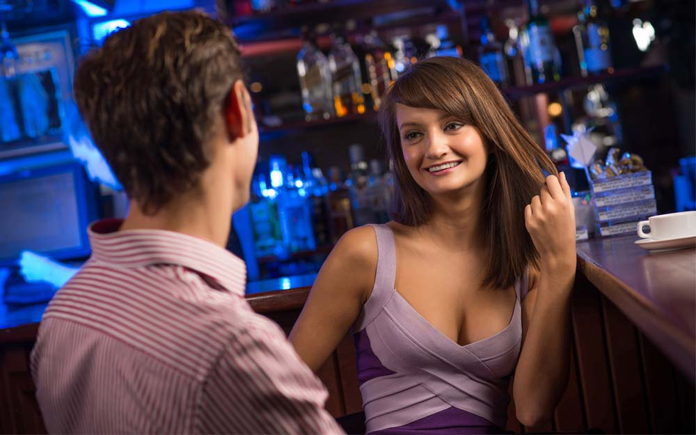 man seducing good looking woman at bar